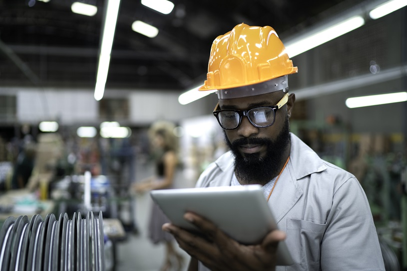 Manufacturer using tablet and working in factory