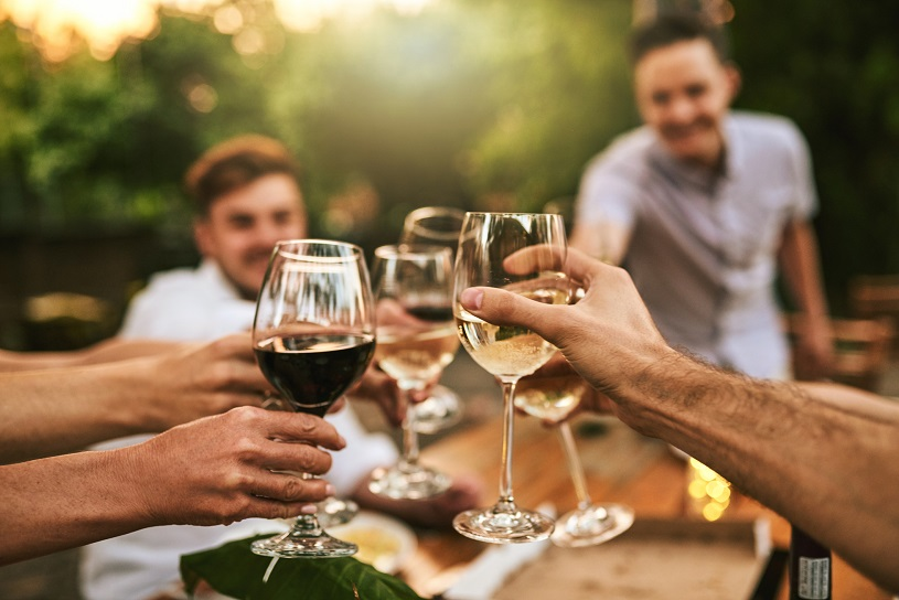 Shot of friends drinking wine outdoors