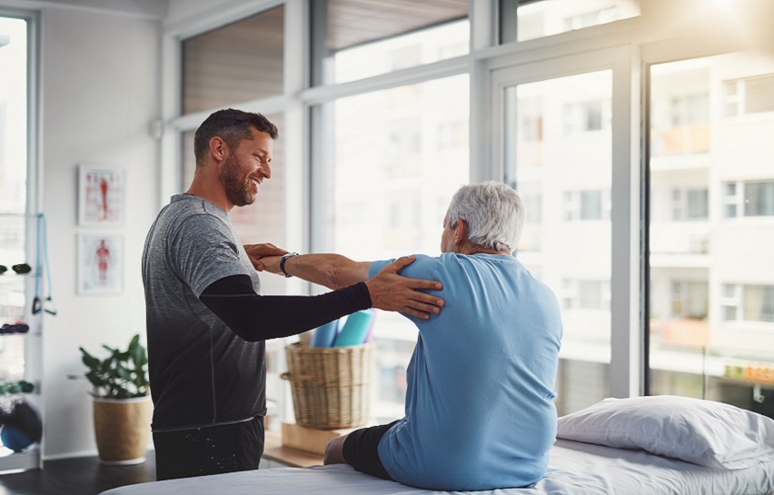 Physiotherapist assisting a senior patient in recovery