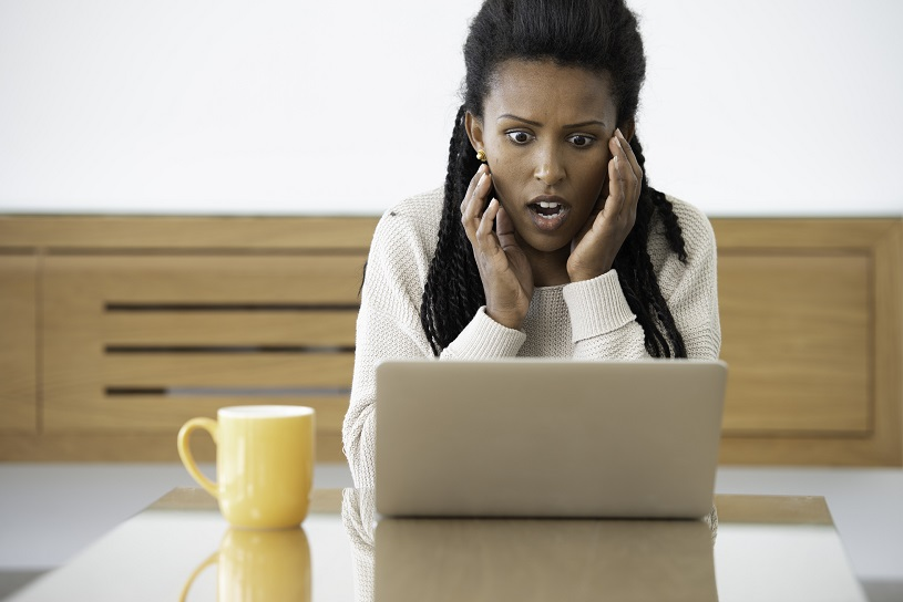 A shocked woman on a Zoom meeting working from home