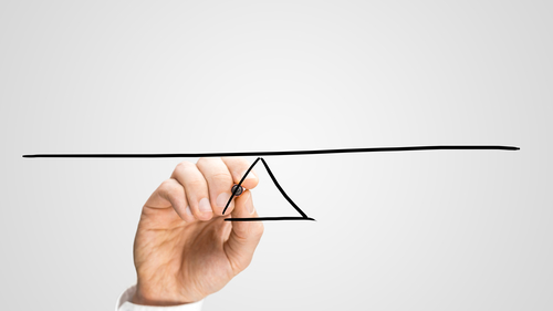 Man drawing a seesaw to demonstrate the concept of a lever and fulcrum, of balance, equilibrium and equality on a grey background with copyspace.