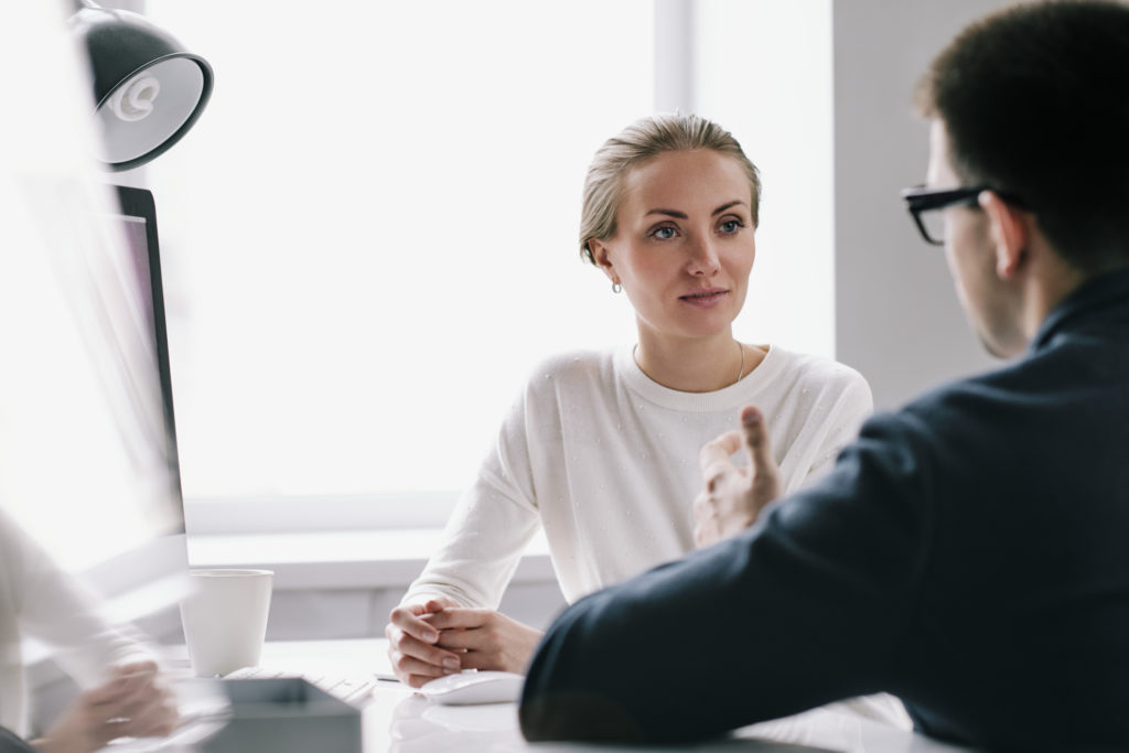 Waist-up portrait of confident young HR manager sitting at office desk while conducting interview with male applicant for position