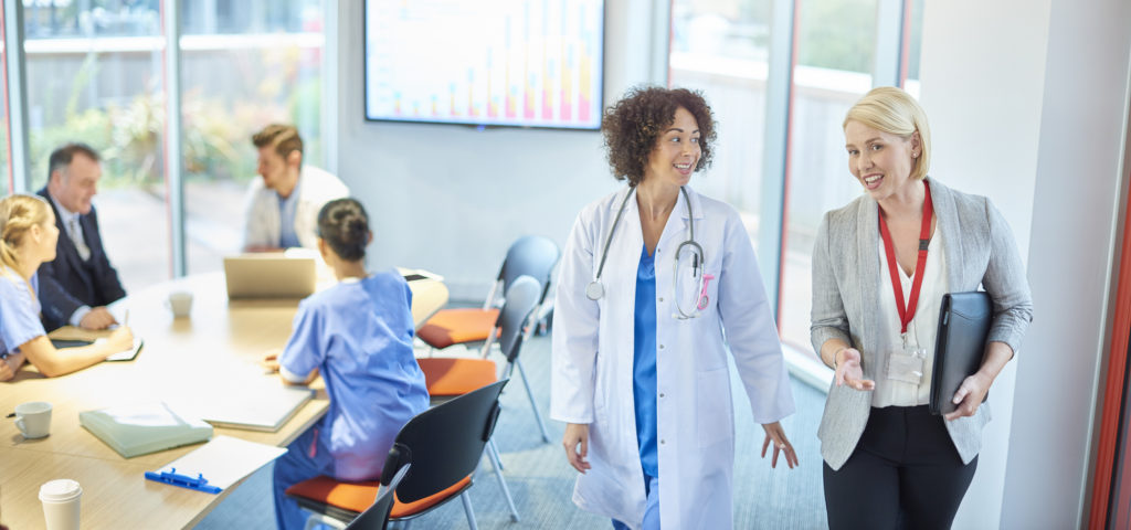 a businesswoman chats with a doctor as they leave a boardroom meeting in a hospital