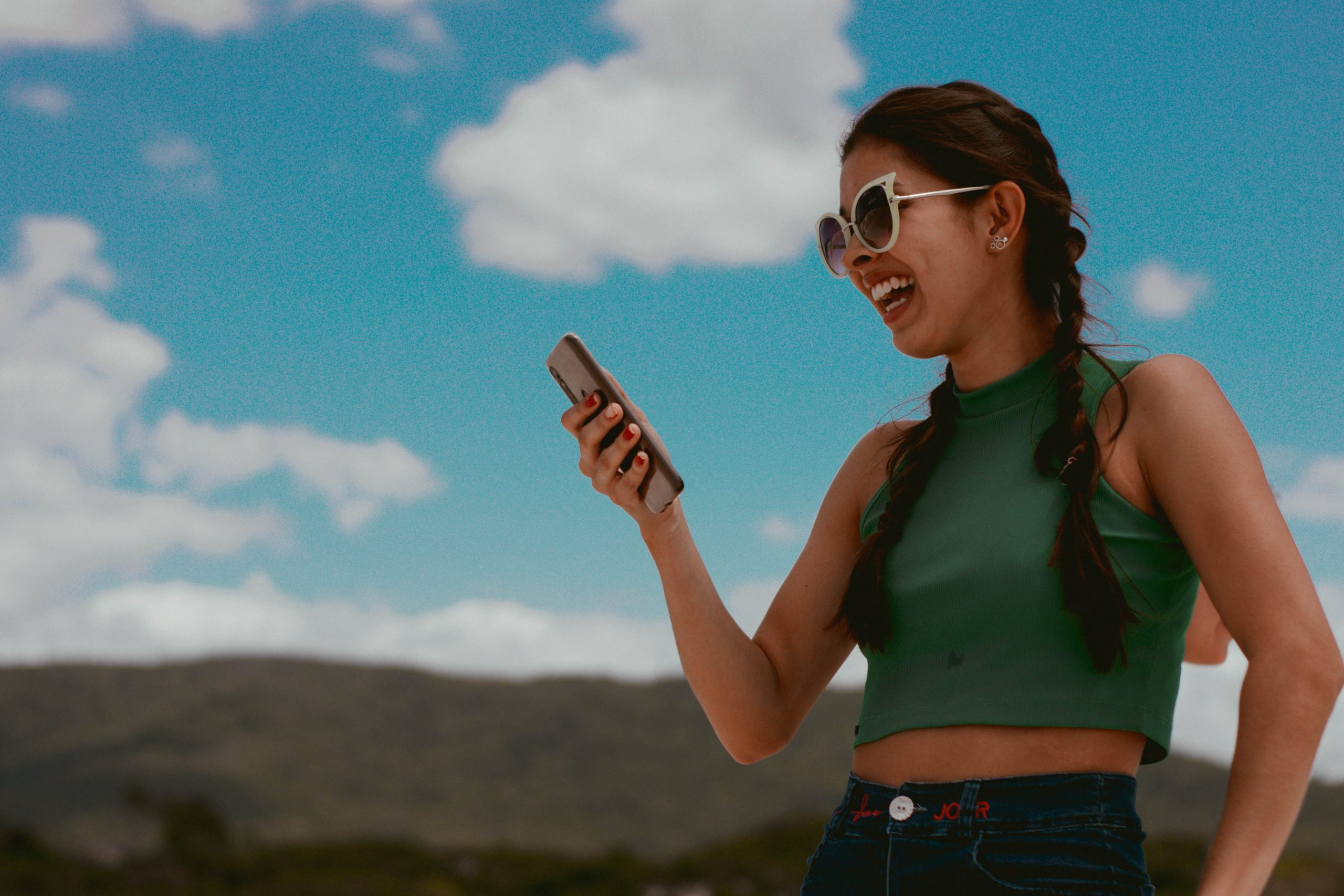 woman in green tank top holding smartphone during daytime