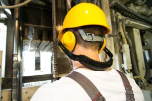 Worker in safety hat and headphones working behind machine on a factory image - spinifex-applyflow